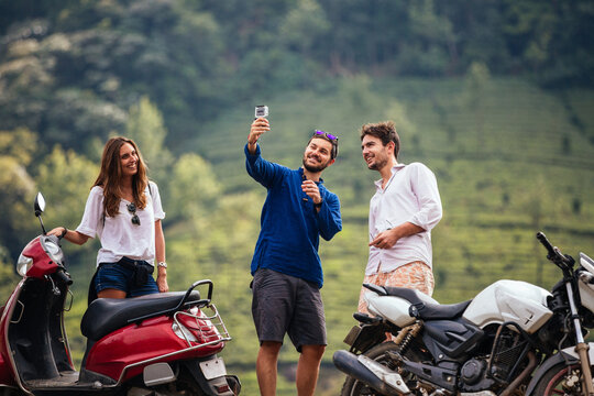 Three young friends standing next to motorbikes in front of a hill of tea plantations taking a selfie picture