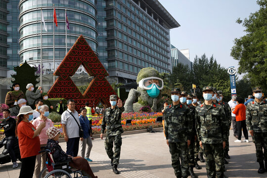 Paramilitary police officers wearing face masks march past a floral installation featuring medical workers, volunteers, scientists and military soldiers in the fight against the coronavirus disease (COVID-19), in Beijing