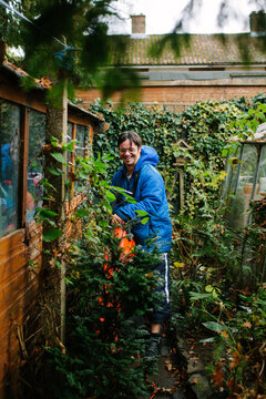Man with learning disabilities using a leaf blower in a garden.
