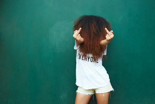 Young woman with face covered in curly hair showing middle fingers