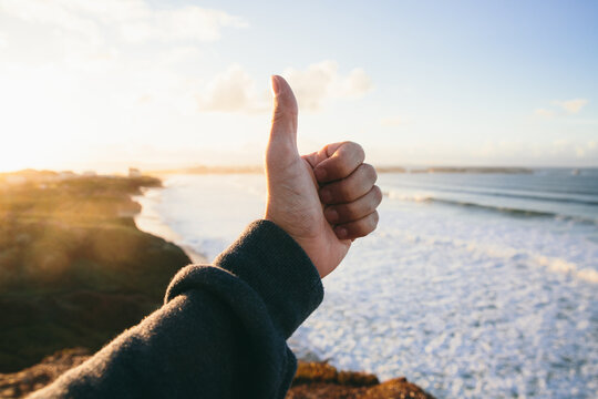 Male hand doing a thumbs up in front of beautiful scenic views of a natural sea shore at sunset