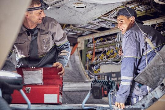 Caucasian men mechanics and technicians are repairing aircraft in the indoors