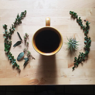 Yellow coffee mug surrounded by green