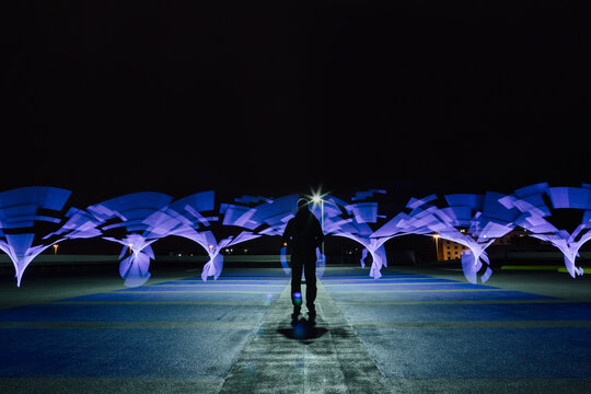 A silhouetted figure in an empty car park, set against swirls of blue light