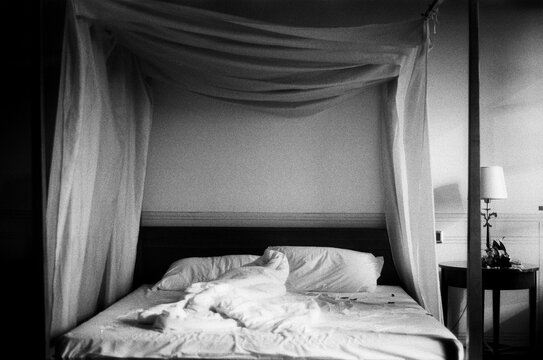 A black and white film photo of white bedroom with king size bed