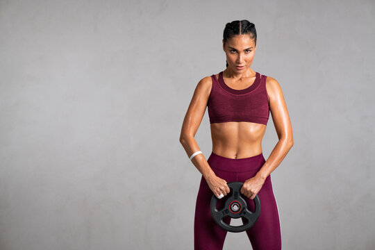 Fit strong mid adult woman lifting weights on grey wall