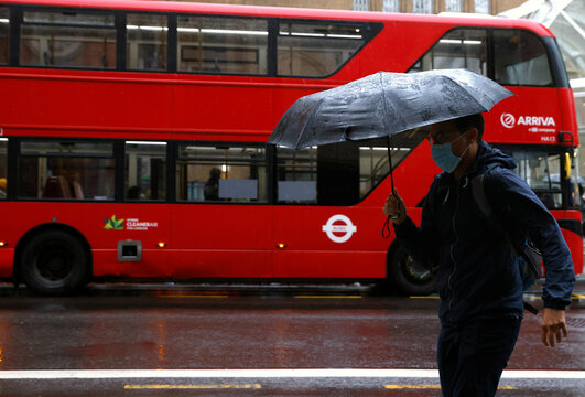 A man with an umbrella walks past a bus in the City of London financial district during the morning rush hour