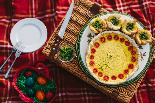 quiche and puff cake filled with cheddar, grated zucchini and cherry tomatoes on colorful picnic place from above