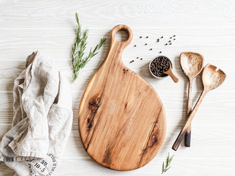 Kitchen cooking flat lay. Spices, wood spoons and wood cutting board for placing your text on a light wood background. Top view. copy space