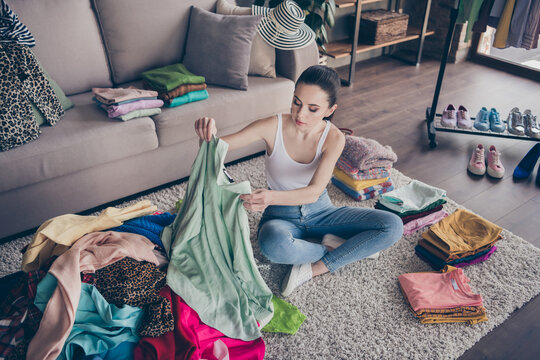 Top above high angle view photo of focused volunteer girl sit floor carpet arrange her used clothes decide what she will give charity in house indoors