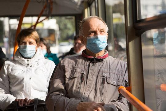 Senior man  wearing medical face mask sitting in the bus transport.