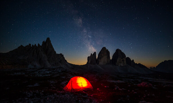 Milky way over Three Peaks of Lavaredo, with lighted camping tent on the foreground