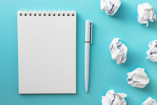Blank notepad, pen and crumpled paper balls on bright blue background. Writing message. Вrawing up a plan. New or bad idea concept. Draw up plan. Flat lay, top view, copy space.