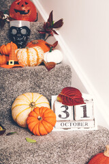 Different types of pumpkins and decorations on stairs indoor. New Normal or Halloween during pandemic at home concept. Stay home, be safe.