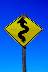 Curves Ahead Roadsign Road Sign Yellow on Blue Sky