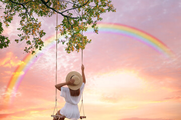 Door stickers Wall Decor With Your Own Photos Dream world. Young woman swinging, rainbow in sunset sky on background