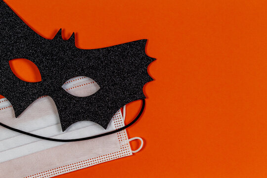 Black glitter halloween eye mask and medical protective face mask on orange background. Halloween , COVID-19 prevention and new normal concept. Top view