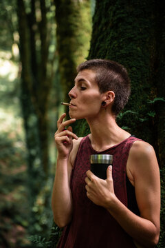 Woman smoking in forest holding camping mug