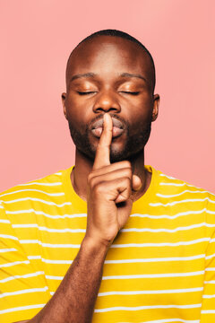 Young black man looking at camera making a shut up sign over a pink background