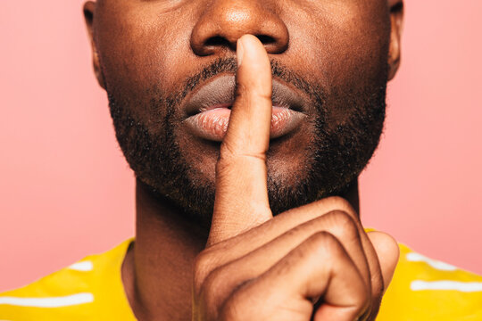 Cropped view of young black man looking at camera making a shut up sign over a pink background