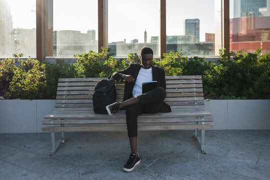 Young businessman using ipad sitting on the bench