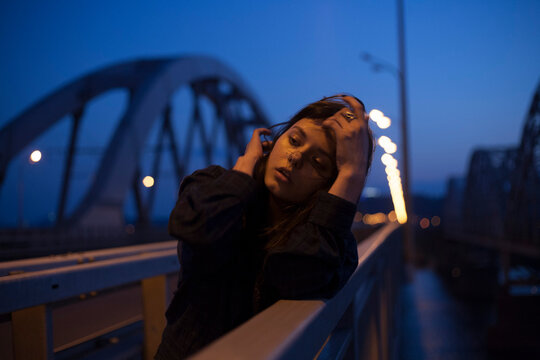 cinematic photo of a girl on a night bridge