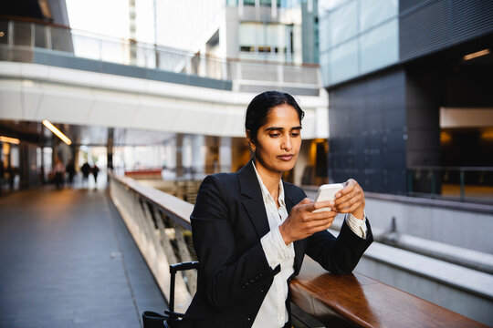 Indian business woman using cellphone out the office building