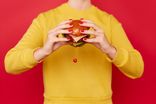 Woman eats burger as it drips tomato sauce. She wears a yellow jumper and stands against a red background.