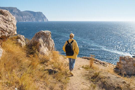 tourist girl walking along a rocky seashore