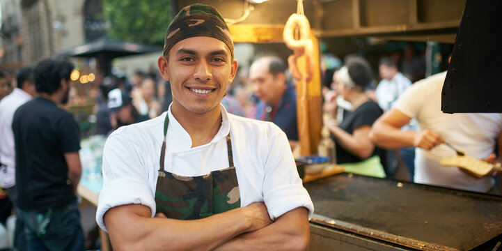 Confident ethnic cook smiling while standing at food market