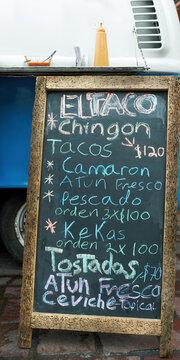 Chalkboard stand with handwritten menu at farmers market