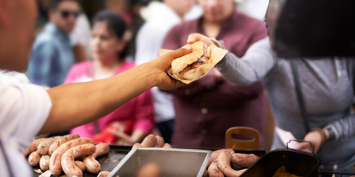 Cook selling sandwich to customer at street food stall