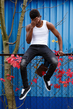 Upset African American guy sitting on metal mesh fence