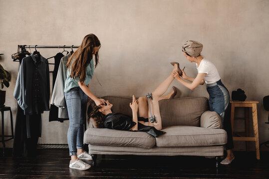 Women preparing model with broken leg for photo session