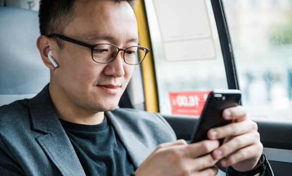 Businessman sitting in taxi and using cell phone