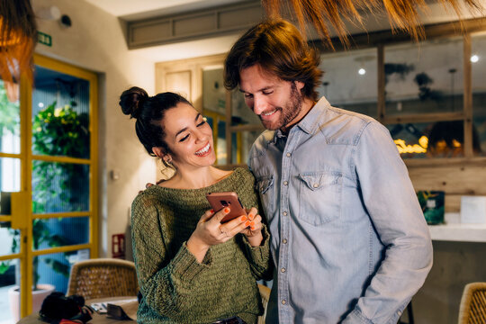 Cheerful woman showing smartphone to boyfriend