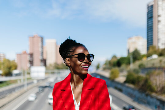 Stylish black woman in red jacket smiling in street