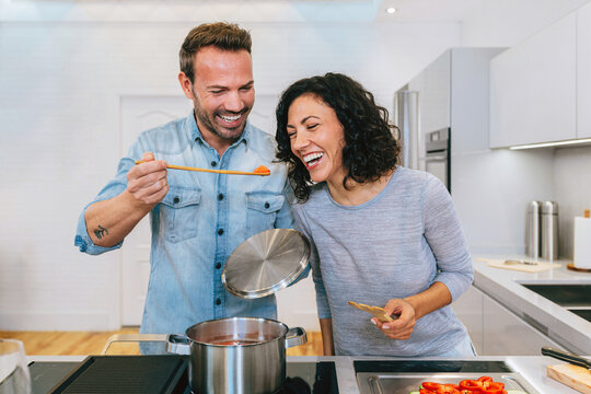 Delighted couple checking dish in saucepan