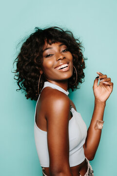 Happy young black woman posing over blue background