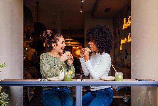 Modern healthy women having lunch in cafe