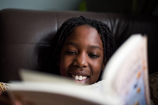 Smiling black girl reading a book