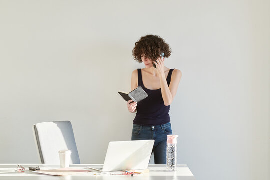 Pensive adult woman reading information in notepad while making