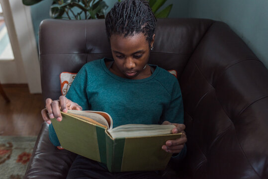 Black girl reading on a couch
