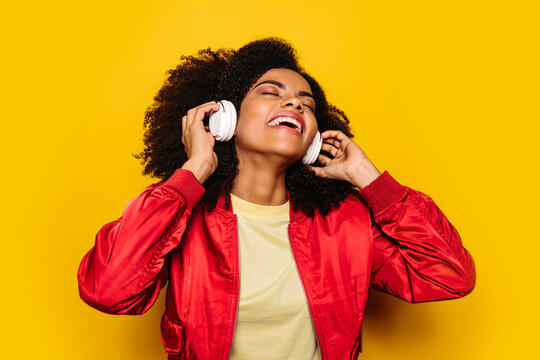 Beautiful afro woman listening to music with white headphones
