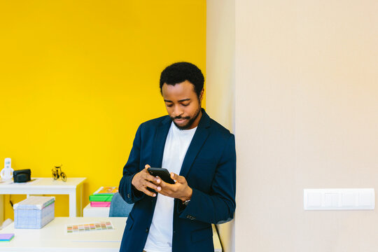 Black man with phone in colorful modern office