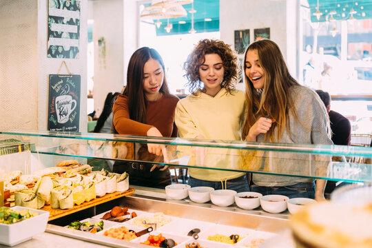 Cheerful women choosing food in cafeteria