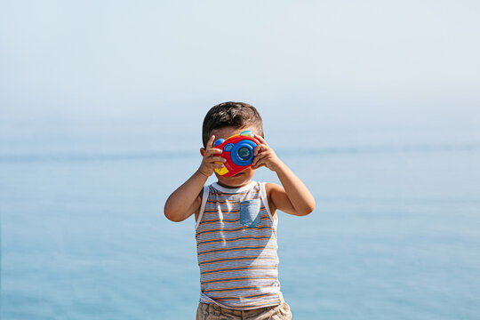 Little funny kid taking photos with a toy camera