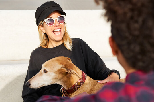 Pretty blonde girl with dog laughing.