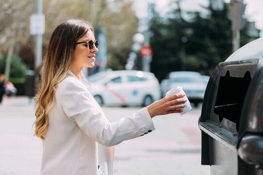 Woman throwing a cardboard glass into a recycling bin