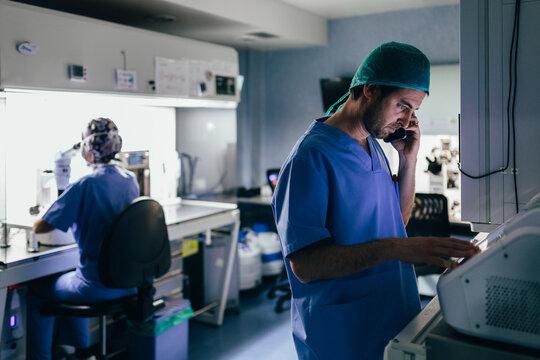 IVF Biologist on phone while manipulating an incubator